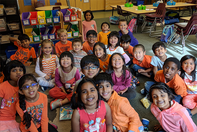A group of students smiling in a classroom